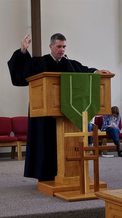 Pastor Rob Standing behind a Wooden Pulpit with Three Crosses in Front of it Praying with One Hand Lifted